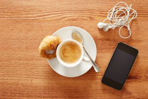 Having coffee and croissants with smartphone and headphones